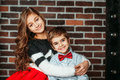 Little boy and girl smiling and hugging on brick background in fashion clothing. Kids brother and sister are happy Royalty Free Stock Photo