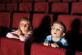 Little boy and girl watching a movie with interest in an empty cinema hall Royalty Free Stock Photography