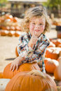 Little boy gives thumbs up at pumpkin patch adorable leaning on a in a rustic ranch setting the Stock Image