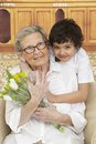 Little boy giving flowers to his grandmother grand mother s day Stock Image