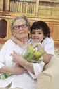 Little boy giving flowers to his grandmother grand mother s day in the library at home Stock Image