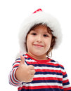 Little boy giving you thumbs up with santa hat on head Royalty Free Stock Photography