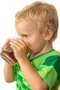 Little boy in a green T-shirt happily drinking tea