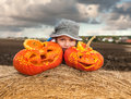 Little boy with halloween pumpkins two carved on a roll of hay Royalty Free Stock Images