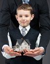 Little boy and hands keeping house model close up of somebody s concept of real estate business Stock Photo