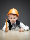 Little boy in hard hat with home model and ruler portrait of on grey background concept of real estate engineering Stock Images