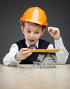 Little boy in hard hat with house model and ruler portrait of on grey background concept of real estate engineering Royalty Free Stock Images