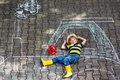 Little boy having fun with tractor picture drawing with chalk happy Royalty Free Stock Photo