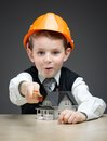 Little boy in headpiece with house model and ruler portrait of on grey background concept of real estate engineering Stock Photo