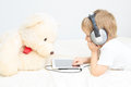 Little boy with headset using touch pad in teddy at home Royalty Free Stock Image