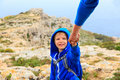 Little boy helped by parent on hiking in mountains Royalty Free Stock Photo