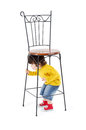 Little boy hides under high wrought iron chair isolated on white background Royalty Free Stock Photos