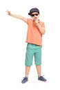 Little boy in hip hop outfit rapping on a microphone full length portrait of and gesturing with his hand isolated white Royalty Free Stock Photography