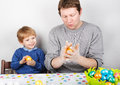 Little boy and his father being happy about selfmade easter eggs toddler having fun with preparing for egg hunt traditional action Royalty Free Stock Images