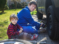 Little boy and his father changing wheel on car with pneumatic wrench Royalty Free Stock Images