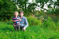 Little boy and his father sitting on grass in summer forest near lake Stock Photography