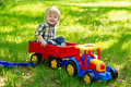 Little boy in his toy truck adorable kid playing the garden sitting the trailer of colorful Royalty Free Stock Image