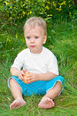 Little boy holding an apple sitting in the grass and Stock Photo