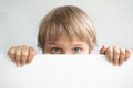 Little boy holding blank white sign or placard hiding his face Royalty Free Stock Photo