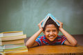 Little boy holding book over head in classroom portrait of cute Stock Images