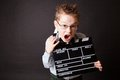 Little boy holding clapper board in hands cinema concept Stock Photos