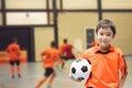 Little boy holding football in futsal gym Royalty Free Stock Photo
