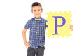 Little boy holding yellow piece of a puzzle isolated on white background Royalty Free Stock Images