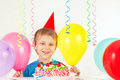 Little boy in holiday hat with birthday cake and balloons Royalty Free Stock Photo