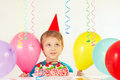 Little boy in holiday hat with festive cake and balloons Royalty Free Stock Photo