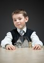 Little boy with home model and pile of coins portrait house on grey background concept real estate money Stock Image