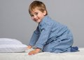 Little boy at home wearing blue pyjamas in bed Stock Images