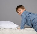 Little boy at home wearing blue pyjamas in bed Royalty Free Stock Image