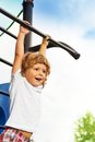 Little boy on horizontal bar close portrait of happy three years old about to hand the playground Royalty Free Stock Image