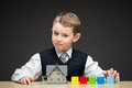 Little boy with house model and blocks portrait of multicolored concept of construction real estate Stock Images