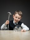 Little boy with house model and hammer portrait of on grey background concept of real estate damage Royalty Free Stock Photography