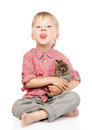 Little boy hugging a kitten showing his tongue isolated on whit Stock Photography