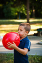 Little boy inflate big red  balloon in park Royalty Free Stock Photo