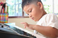 Little boy jouant le piano Photos stock