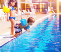 Little boy jumping into the pool cute brother and sister having fun in poolside water amusement luxury beach resort summer Stock Photography