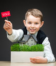 Little boy keeping home model and sold tablet portrait of on grey background concept of real estate deal Stock Photo