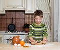 Little boy in the kitchen preparing the dough for cookies using rolling portrait of Stock Photos