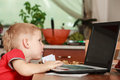 Little boy with laptop on table in home. Royalty Free Stock Photo