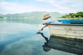 Little boy launch paper ship from old boat on the lake Royalty Free Stock Photo