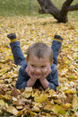 Little boy laying in leaves Stock Images