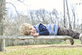 Little boy laying on a weathered wooden swing blonde haired down with peaceful look his face Stock Image