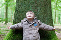 Little boy leaning on big tree looking up and a trunk Stock Images