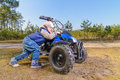 Little boy little boy pushes quad bike in the forest Stock Photos