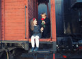 Little boy and the little girl in the retro train gives red rose to Stock Image