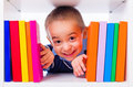 Little boy looking through book shelf cute peeping from behind of colorful books Stock Photo