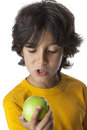 Little boy looking at a green apple on white background Royalty Free Stock Image